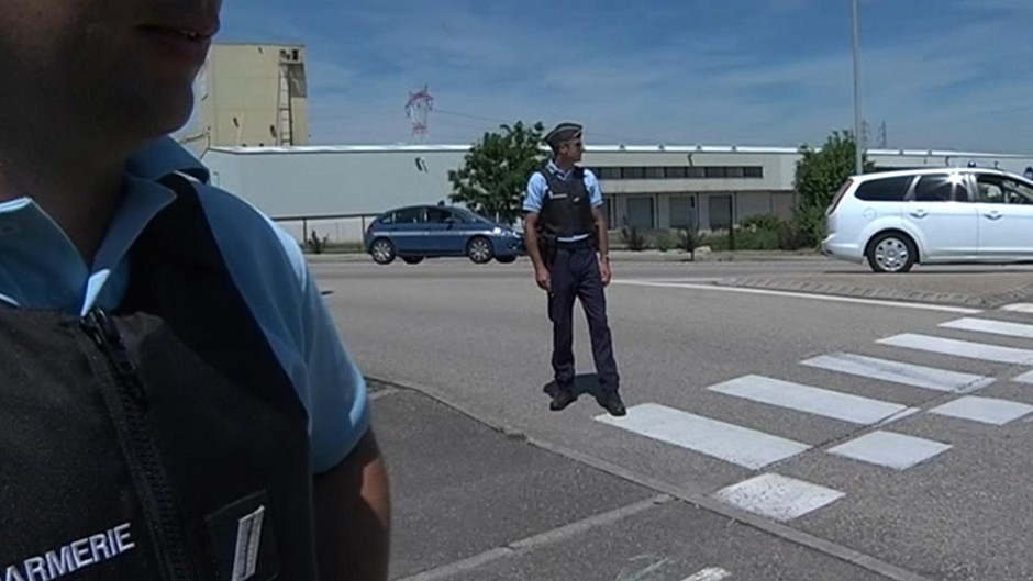 Screen grab from BFM TV shows police standing at the scene outside the factory where the man was  beheaded