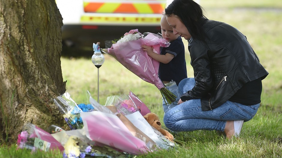 Irana Jackson and her son Finley lay flowers at the scene in Westfield Lane, Mansfield, where a body was found during the search for missing 13-year-old girl Amber Peat