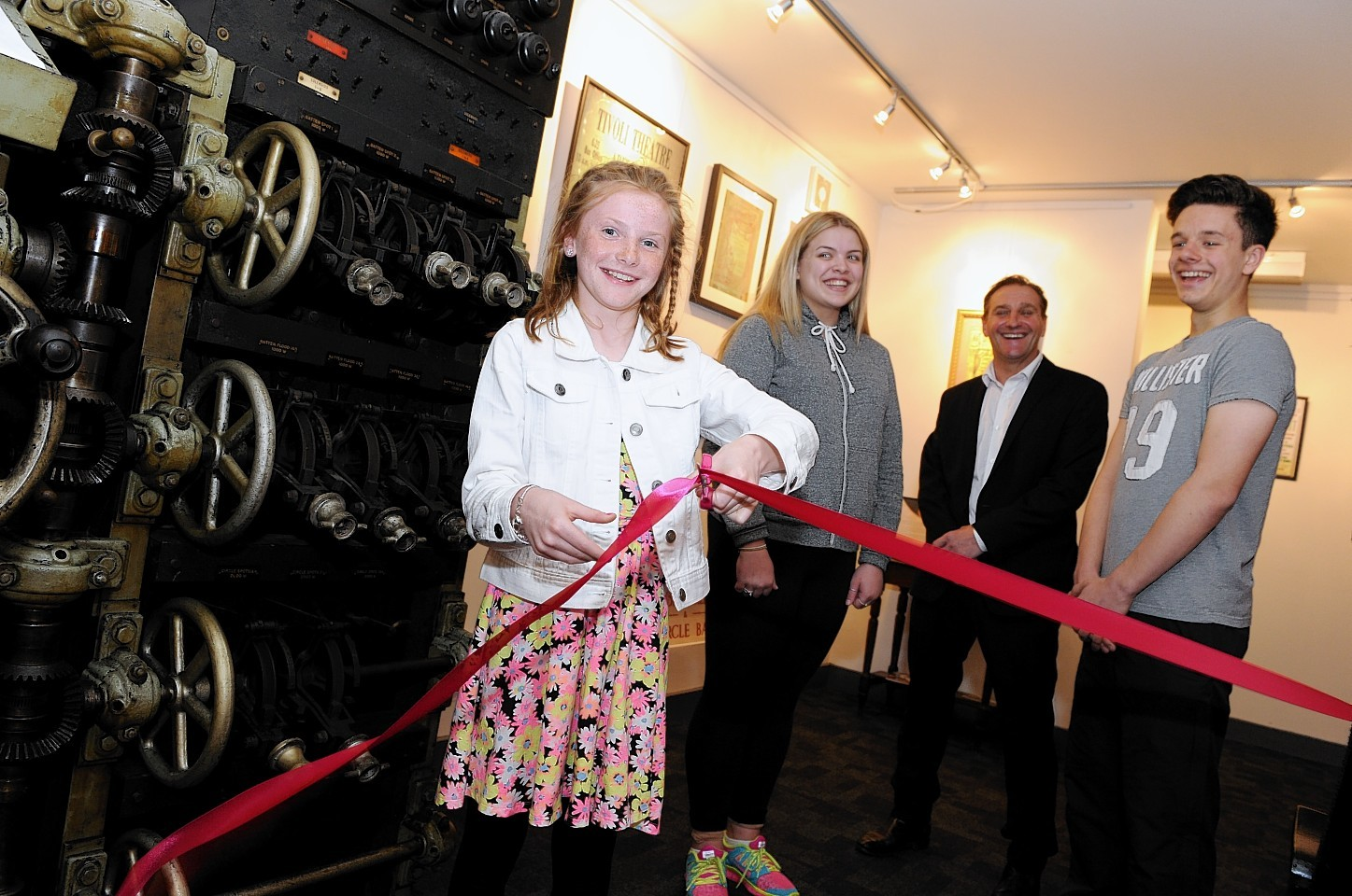 (FROM LEFT) Member of Aberdeen Youth Musical Theatre juniors, Holly Hendry, opening the new Tivoli Theatre museum with AYMT member Indya Greig, managing director Brian Hendry and AYMT member Joe Reid looking on.  Picture by KEVIN EMSLIE