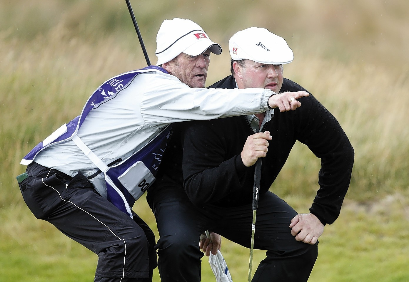 Doak takes advice from his caddy on the 16th