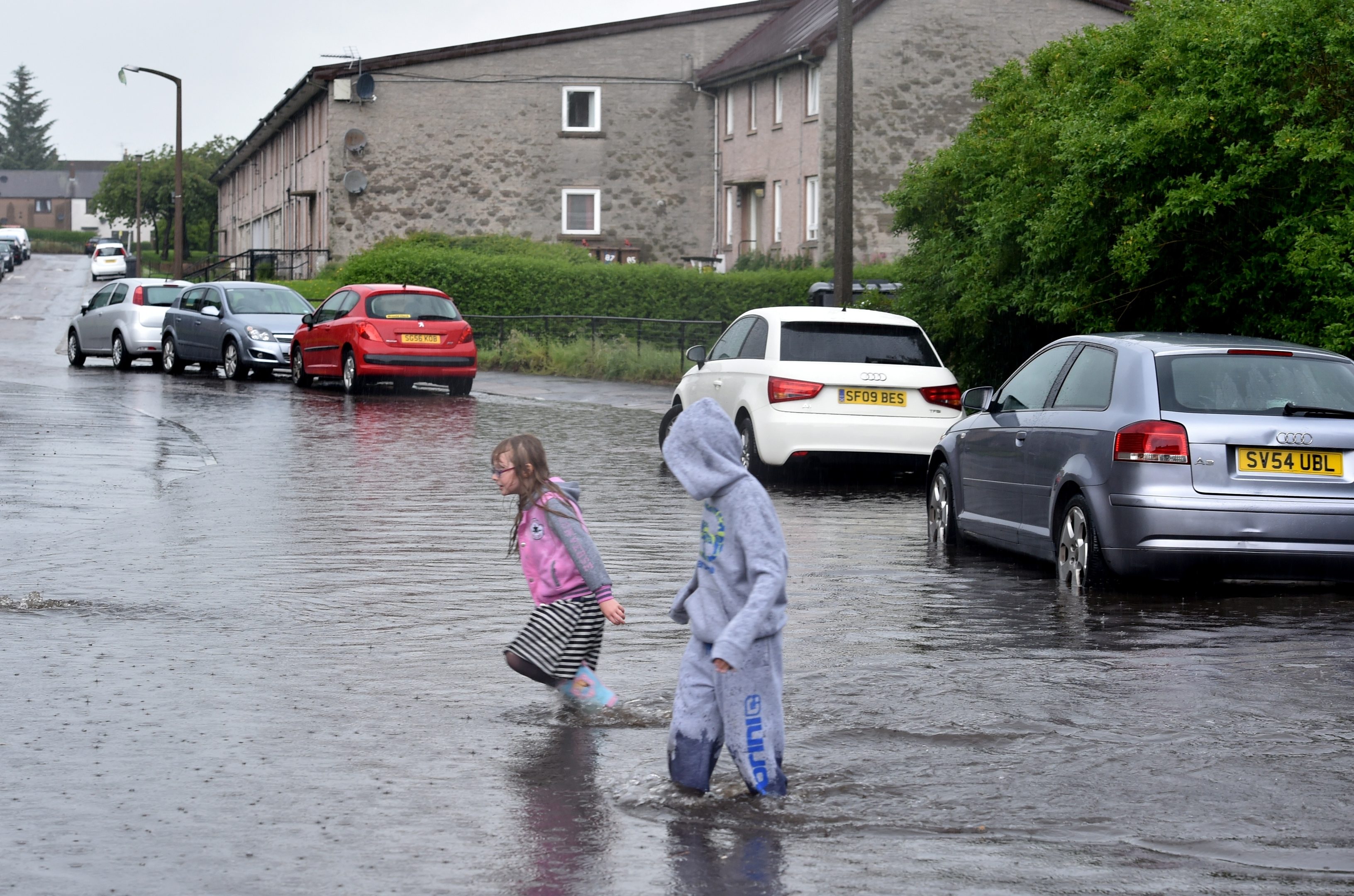 Amy Moir, 8 and Kai Neil 10 enjoy the floods at  Willowpark Crescent. Picture by Colin Rennie