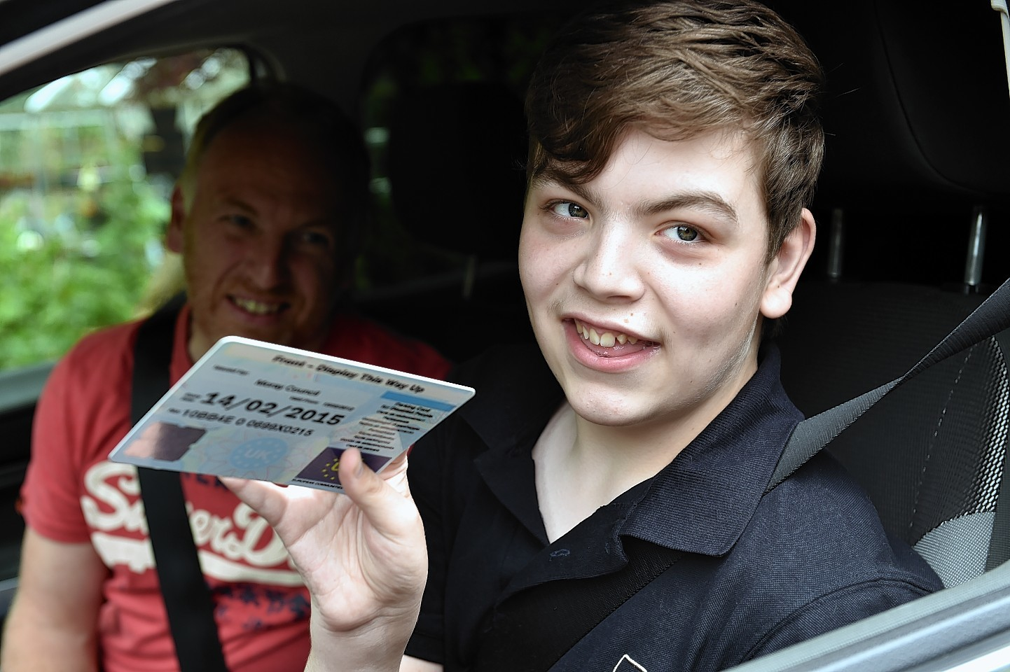 Glyn Morris and his son Gregor, with his expired blue badge.