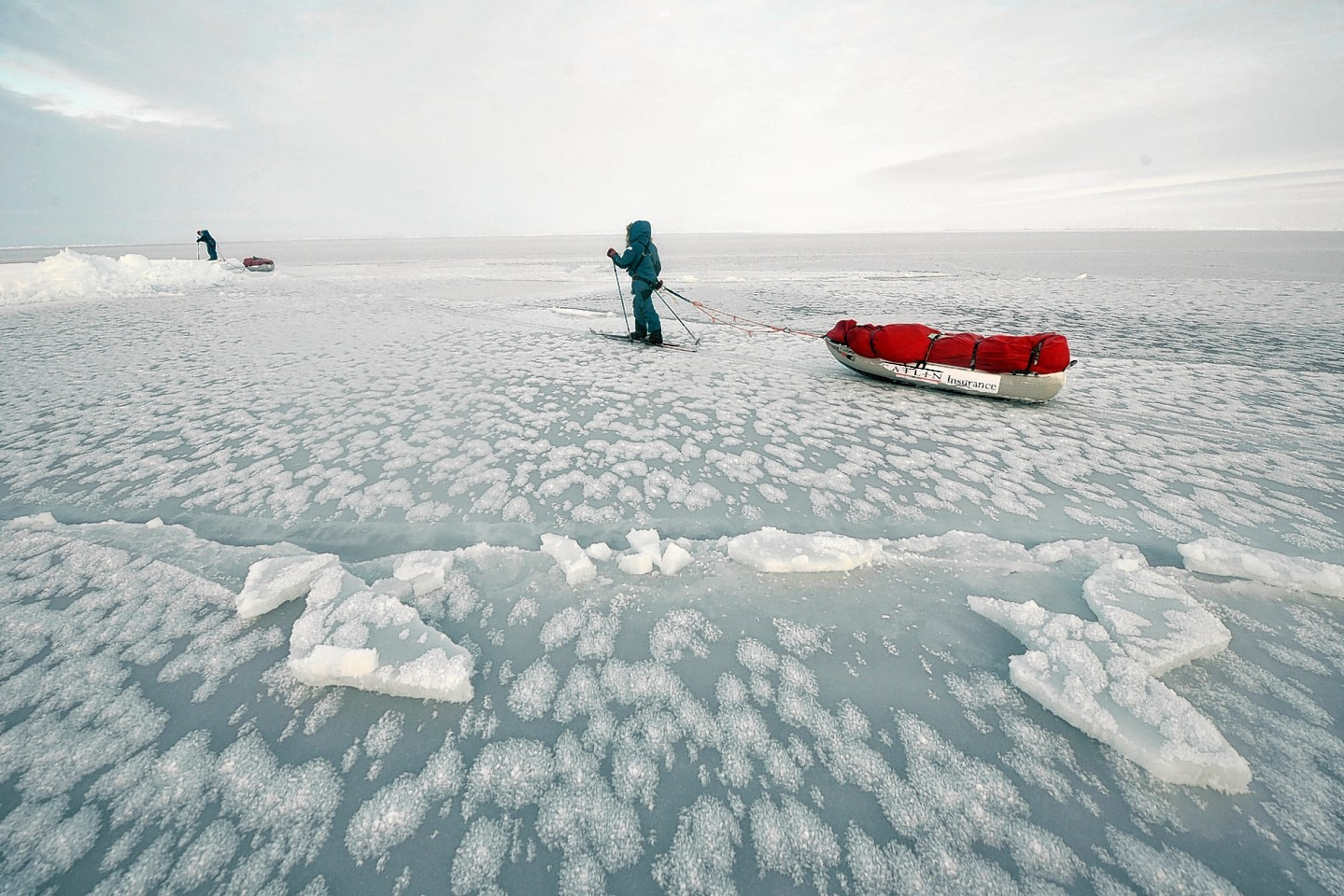 Charlie Paton and a team mate pulling sledge on thin ice in the North Pole.