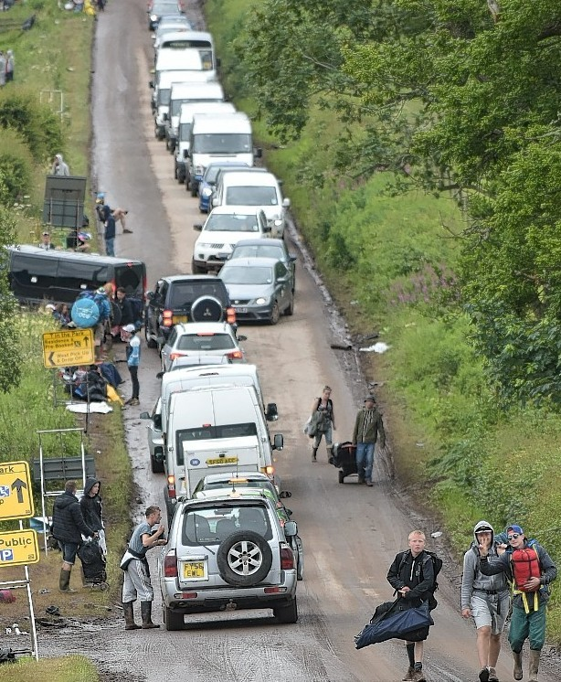 Revellers walking by the side of a gridlocked road as they wait for a lift home from T In The Park.
