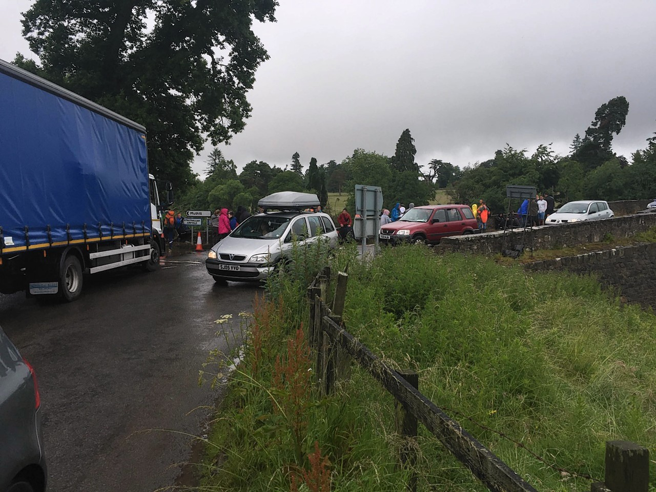 Revellers are seen waiting at a pick up zone as they wait for a lift home from T In The Park in Strathallan