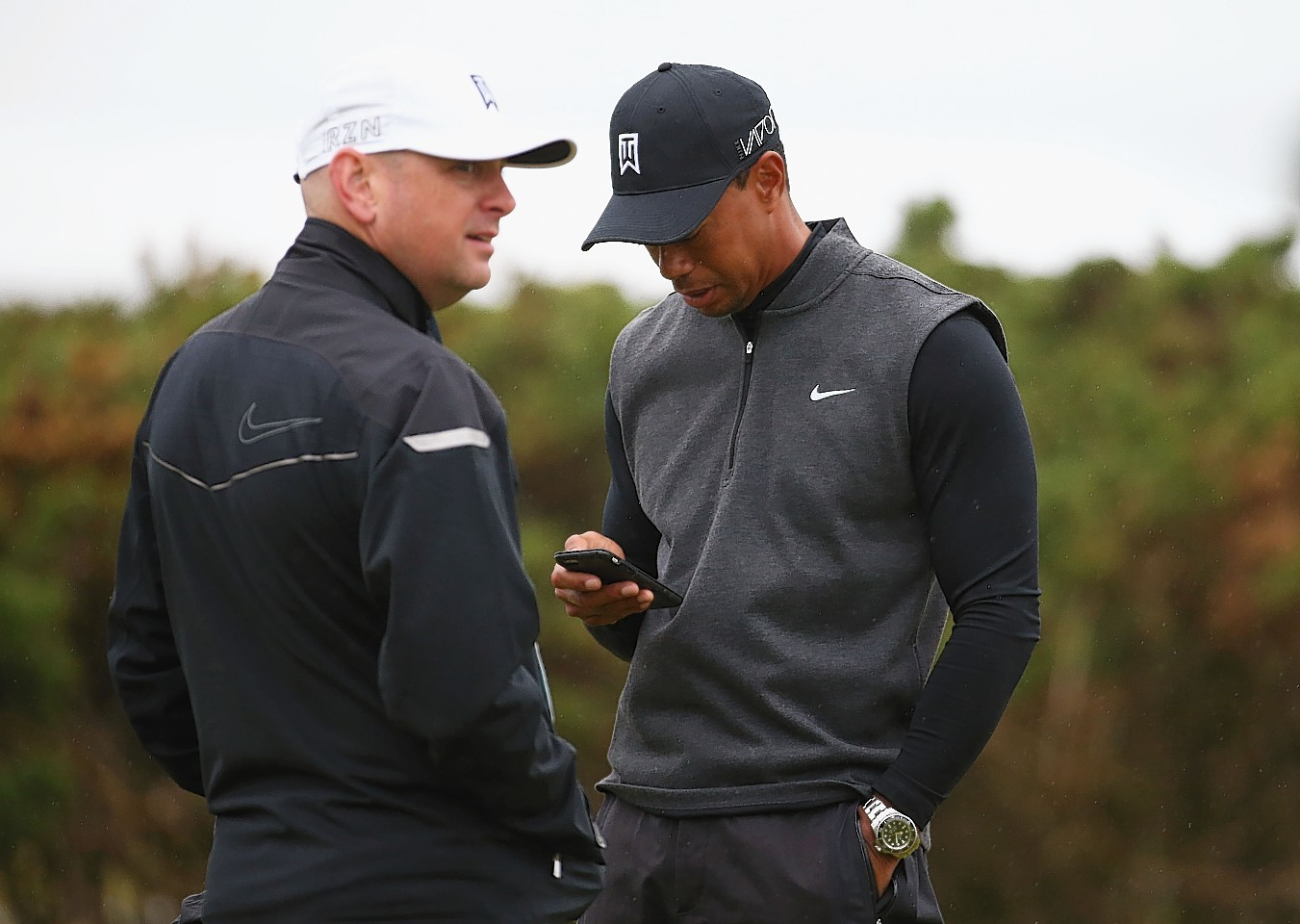 Tiger Woods of the United States looks down at his phone alongside caddie Joe LaCava ahead of the 144th Open Championship at The Old Course