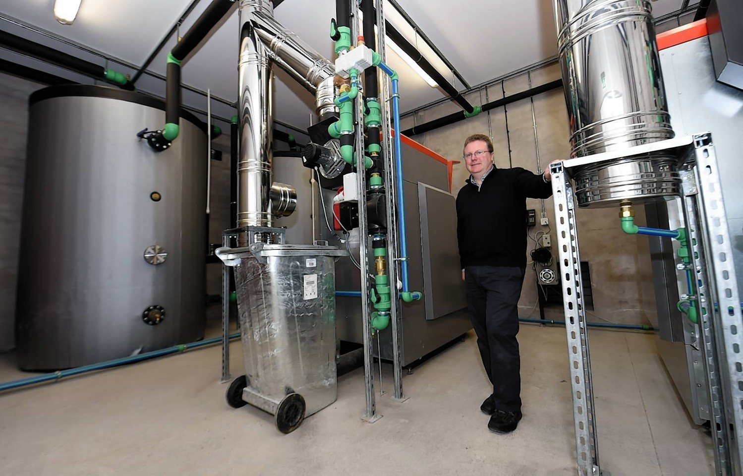 Michael Bruce in the new biomass district heating plant which powers eight properties on the estate