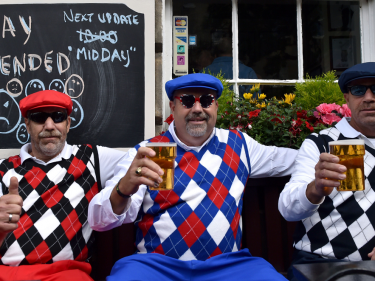 Golf fans enjoy a pint before play is resume at The Open