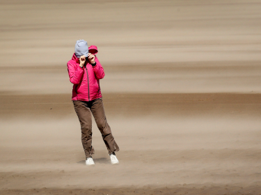 A woman walking on St Andrews beach shields her face from the sand, whipped up by the 40mph winds