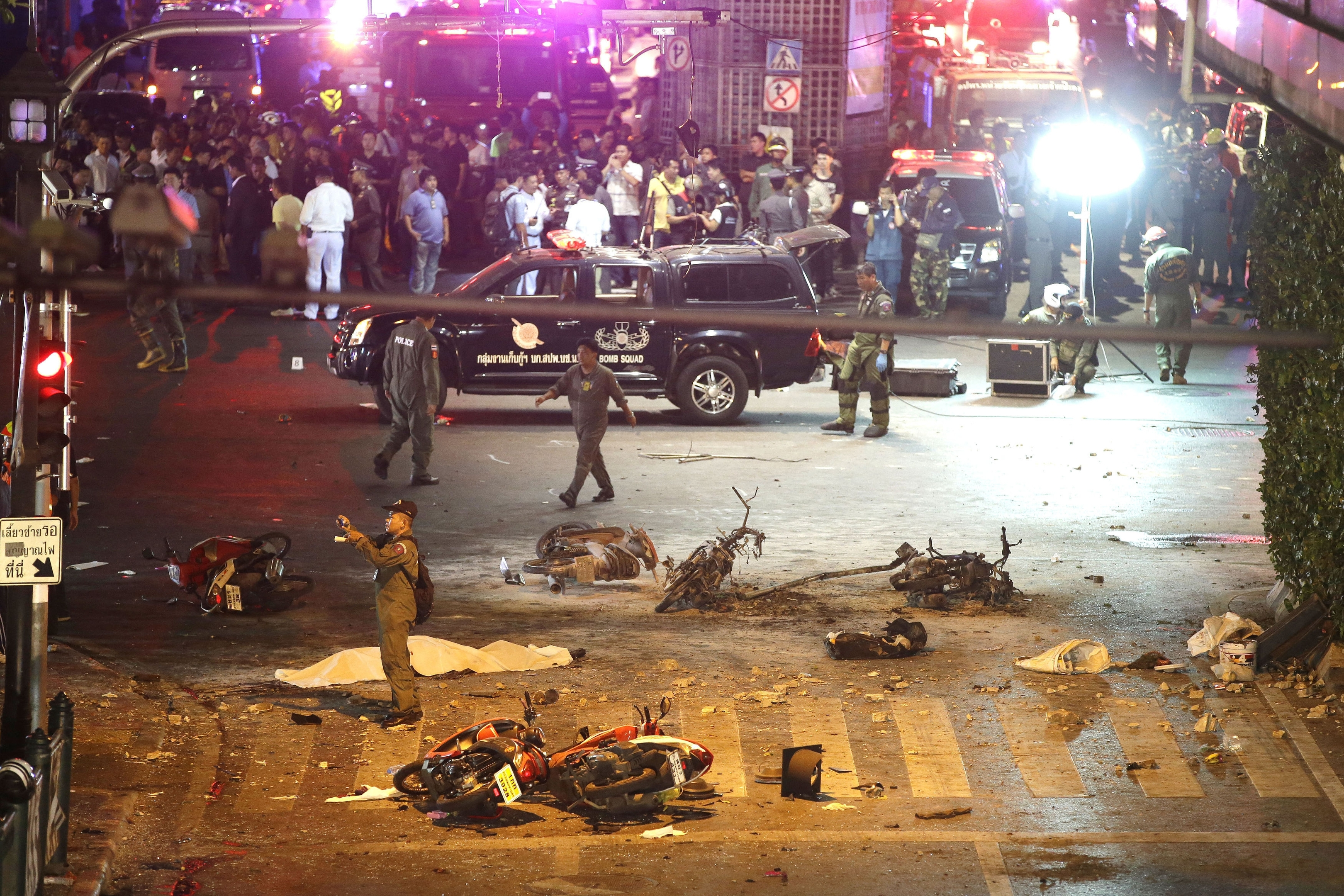 A policeman photographs debris from the explosion in central Bangkok