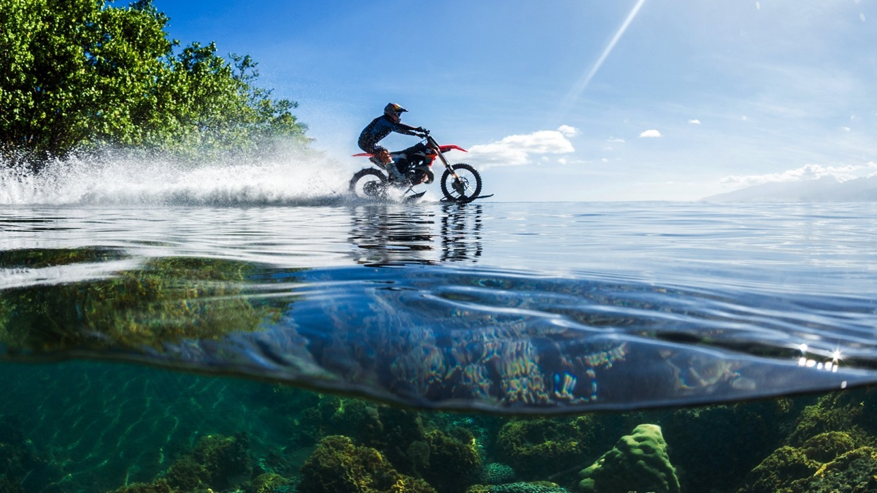 In this April, 2015, photo provided by DC Shoes, daredevil Robbie Maddison in his latest stunt rides his motorcycle across waves in Tahiti, French Polynesia, using ski-like devices on his wheels.  (Tim McKenna/DC Shoes via AP)