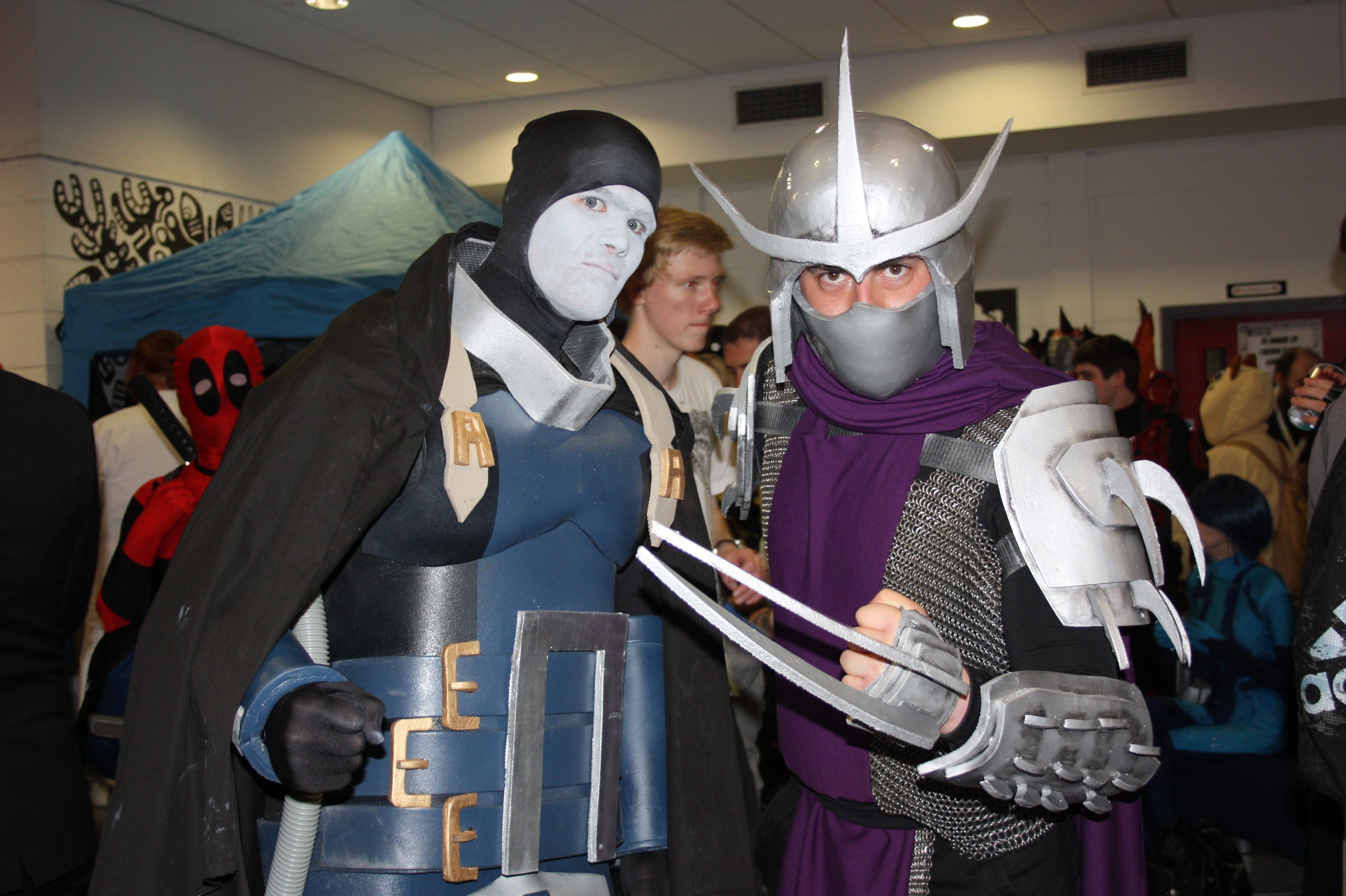 Left to right for spikey blue-faced man in a black hood, and spikey-helmet man with hand-claw: Niall Taylor as Marvel Comics' Apocalypse, and his friend Tim Shread as Shredder from Teenage Mutant Ninja Turtles.