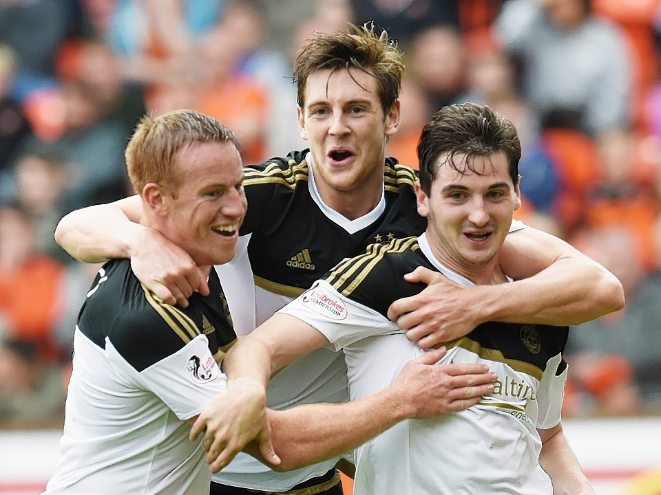 McLean is mobbed by Adam Rooney and Ash Taylor after netting the winner for Aberdeen