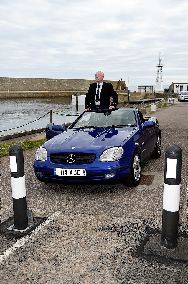Douglas Coutts and his Mercedes blocked by the bollards at Lossiemouth Harbour. Picture by Gordon Lennox