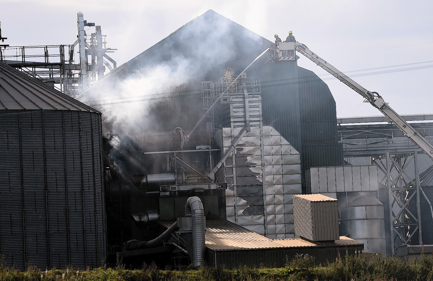Firefighters hose down the fire in a grain drier at Tore, near Inverness. Picture by Gordon Lennox