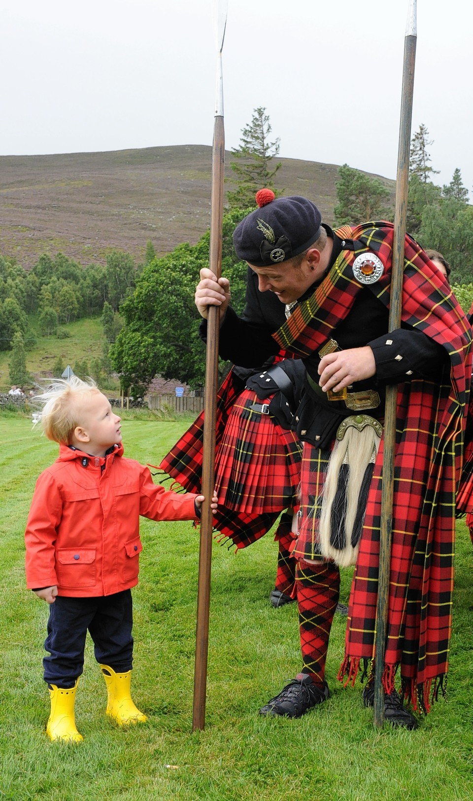 A Lonach Highlander chats to one of Gairnshiel Lodge's younger holiday-makers