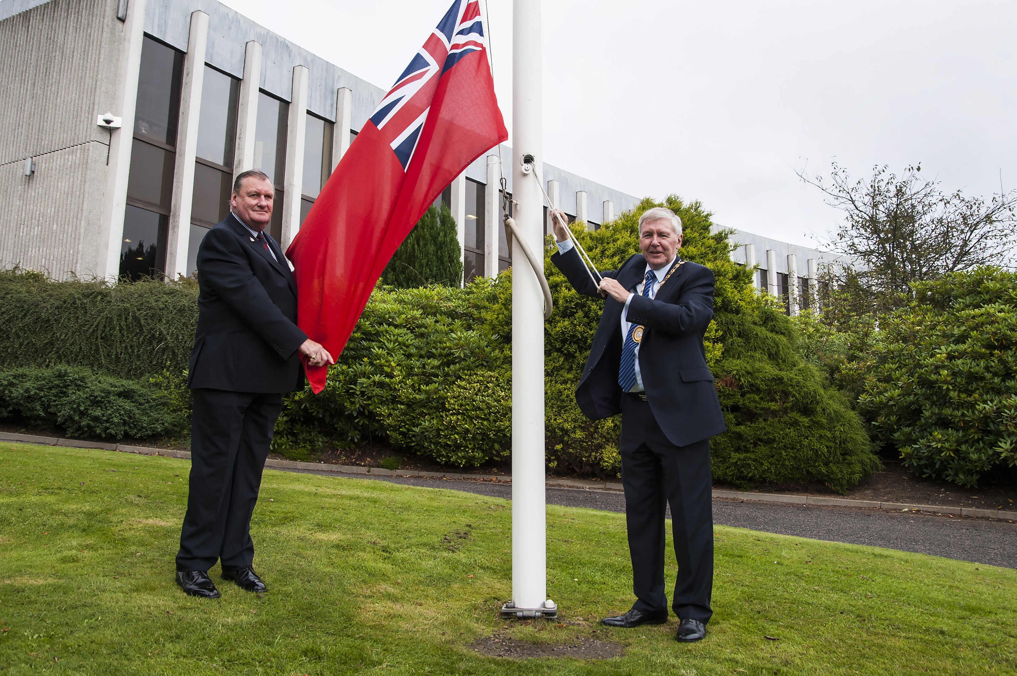 Councillors Allan Hendry and Hamish Vernal raise the red ensign of the Merchant Navy