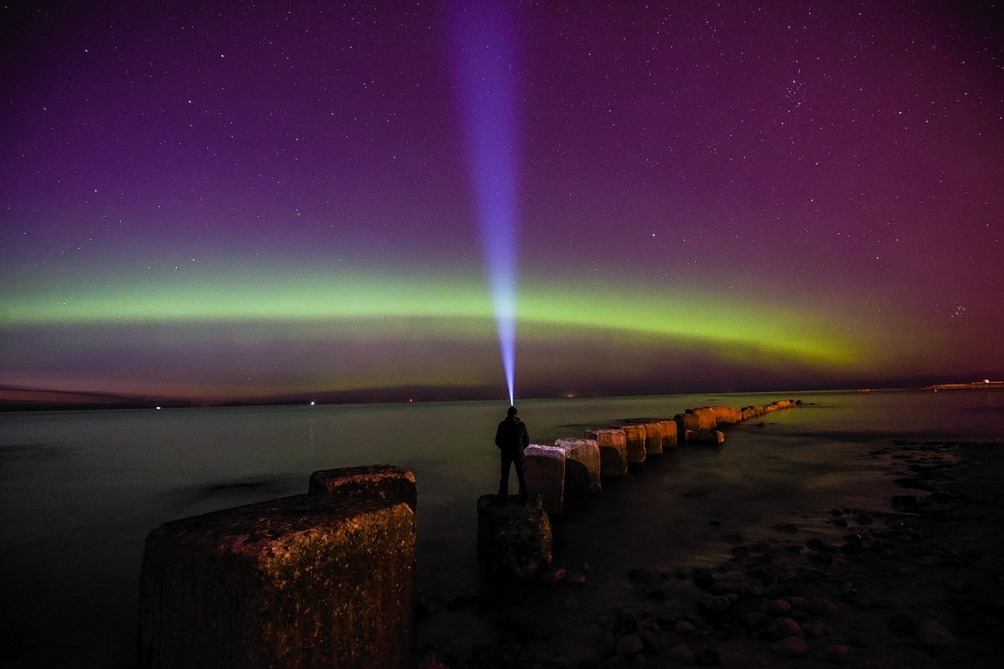 A man wearing a headtorch looks out towards the Aurora Borealis in Lossiemouth, Moray
