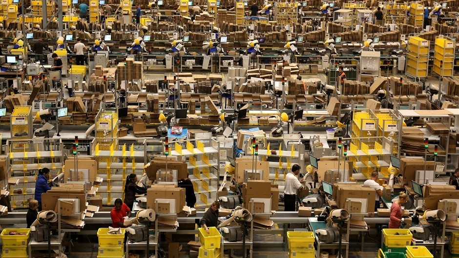 Workers packing orders on the warehouse floor at the Amazon UK Fulfilment Centre in Peterborough
