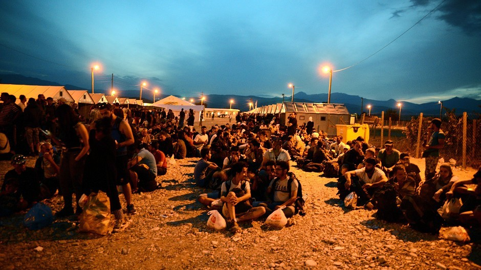 People sit on the ground at a refugee camp in  southern Macedonia