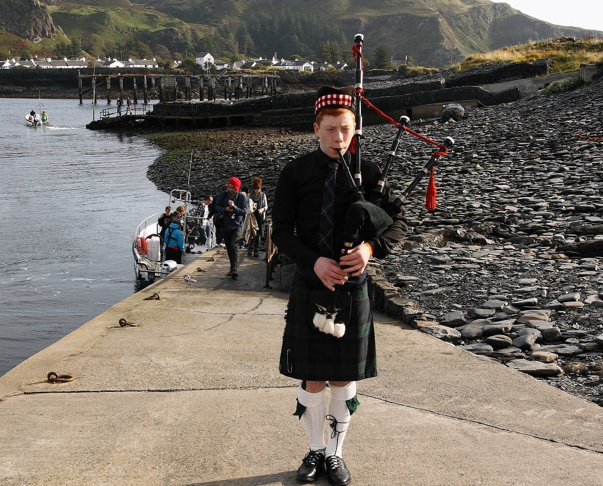 Piper Rory Hunter welcomes spectators and competitors to Easdale island as they arrive for the championships