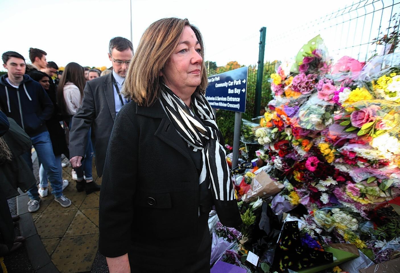 Cults Academy head teacher Anna Muirhead views tributes left outside the school