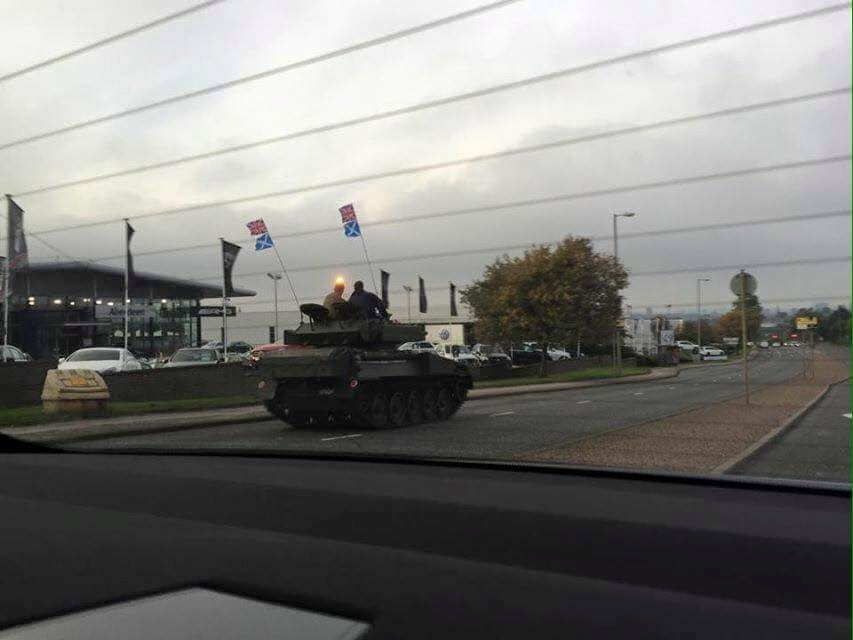 Army tank seen cruising down city road