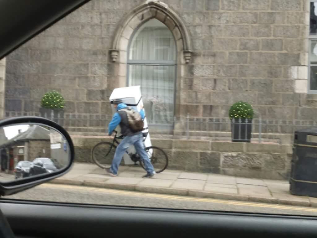 Man transports massive fridge with bike