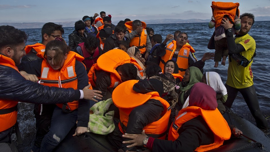 Refugees arrive on a dinghy from the Turkish coast to the Greek island of Lesbos (AP)