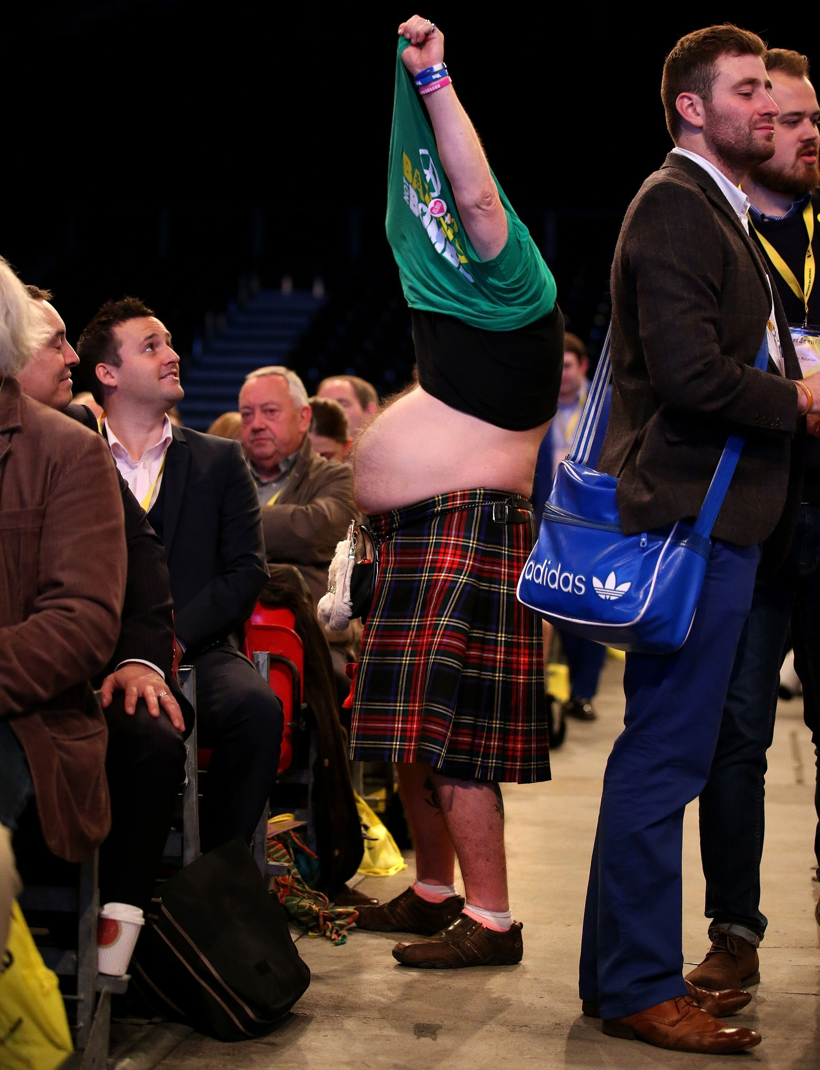 SNP supporter Steve Davies changing his t-shirt in the conference hall at the SNP National Conference