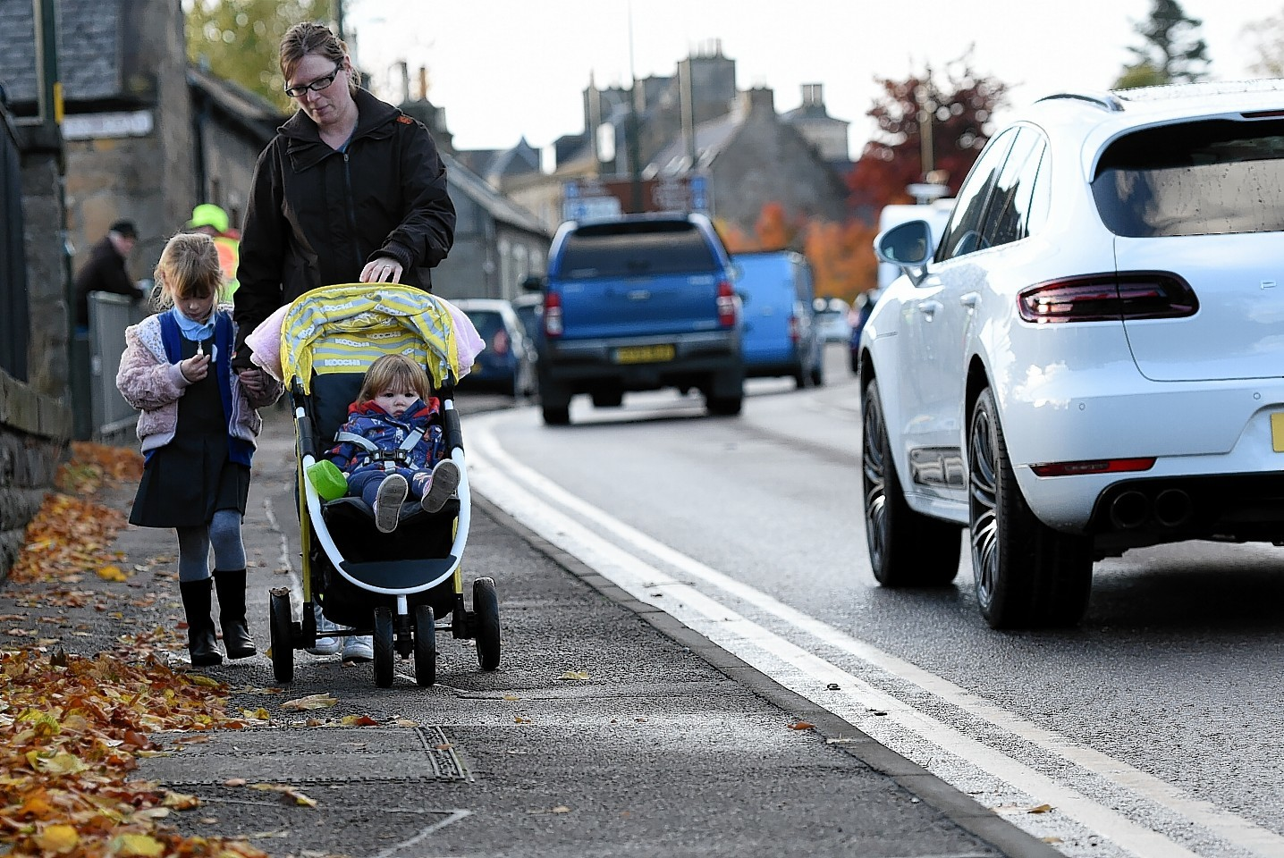 Sarah Candy with her daughters, Sophie, left, and Emily, on their way to school next to the A96 in Elgin.