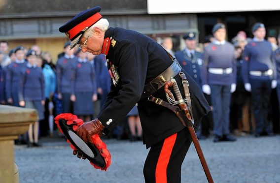 The Lord Lieutenant of Moray, Lt Col Grenville Johnston, lays a wreath of poppies.