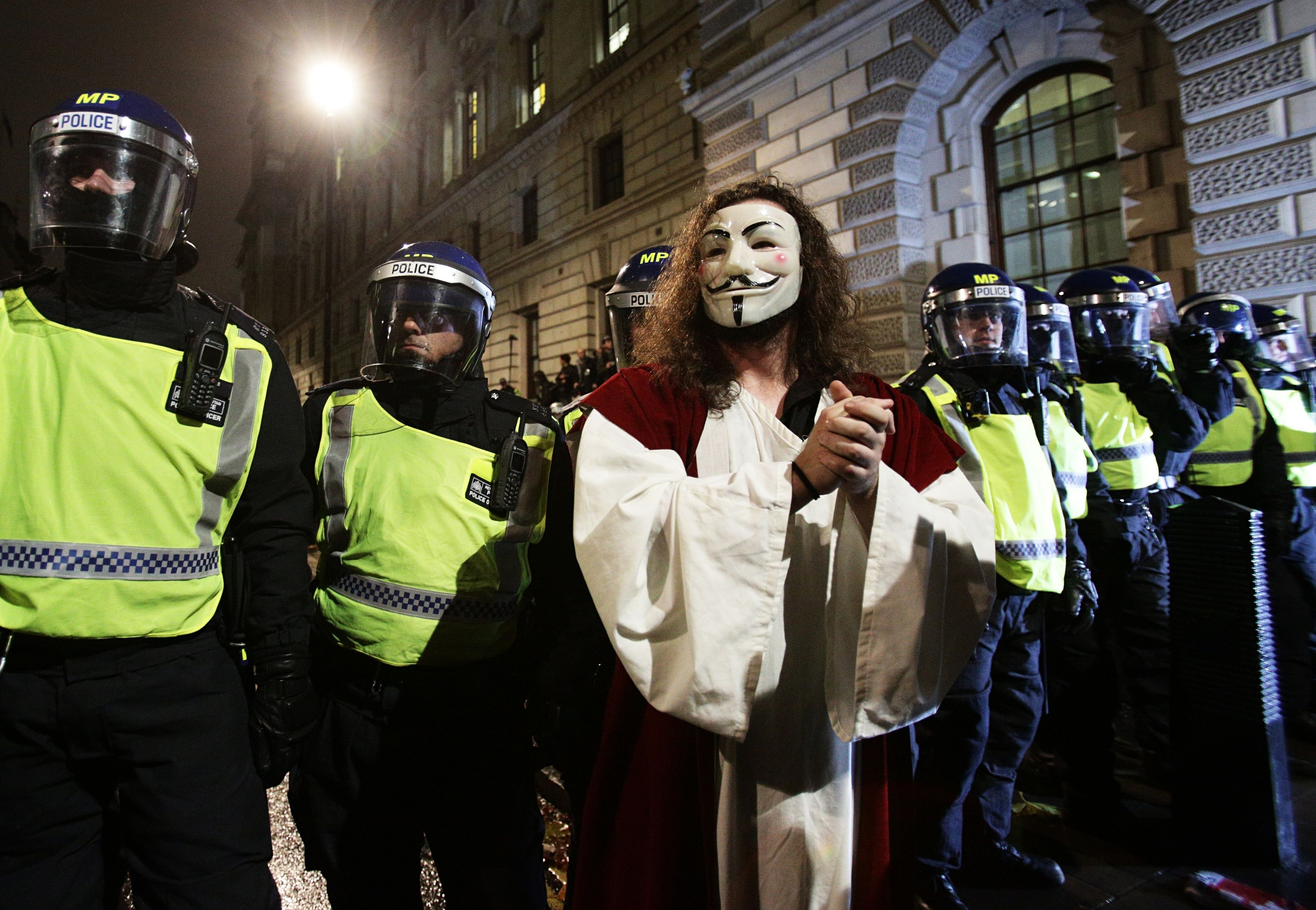 A protester stands in front of police officers during the Million Mask March bonfire night protest in central London, organised by activist group Anonymous.