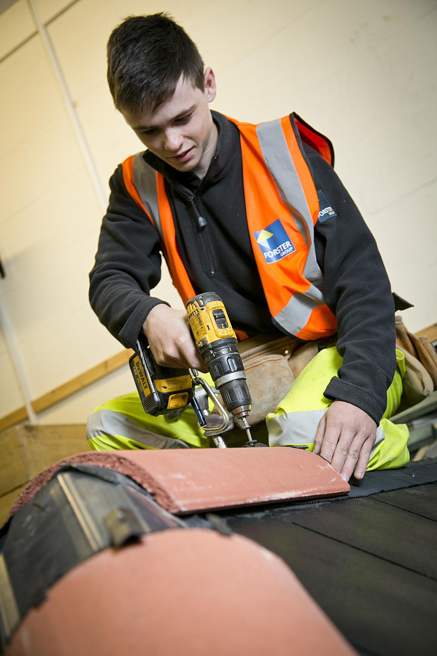 Apprentice Jordan Boyle fixing a ridge tile in Forster's Skills Academy