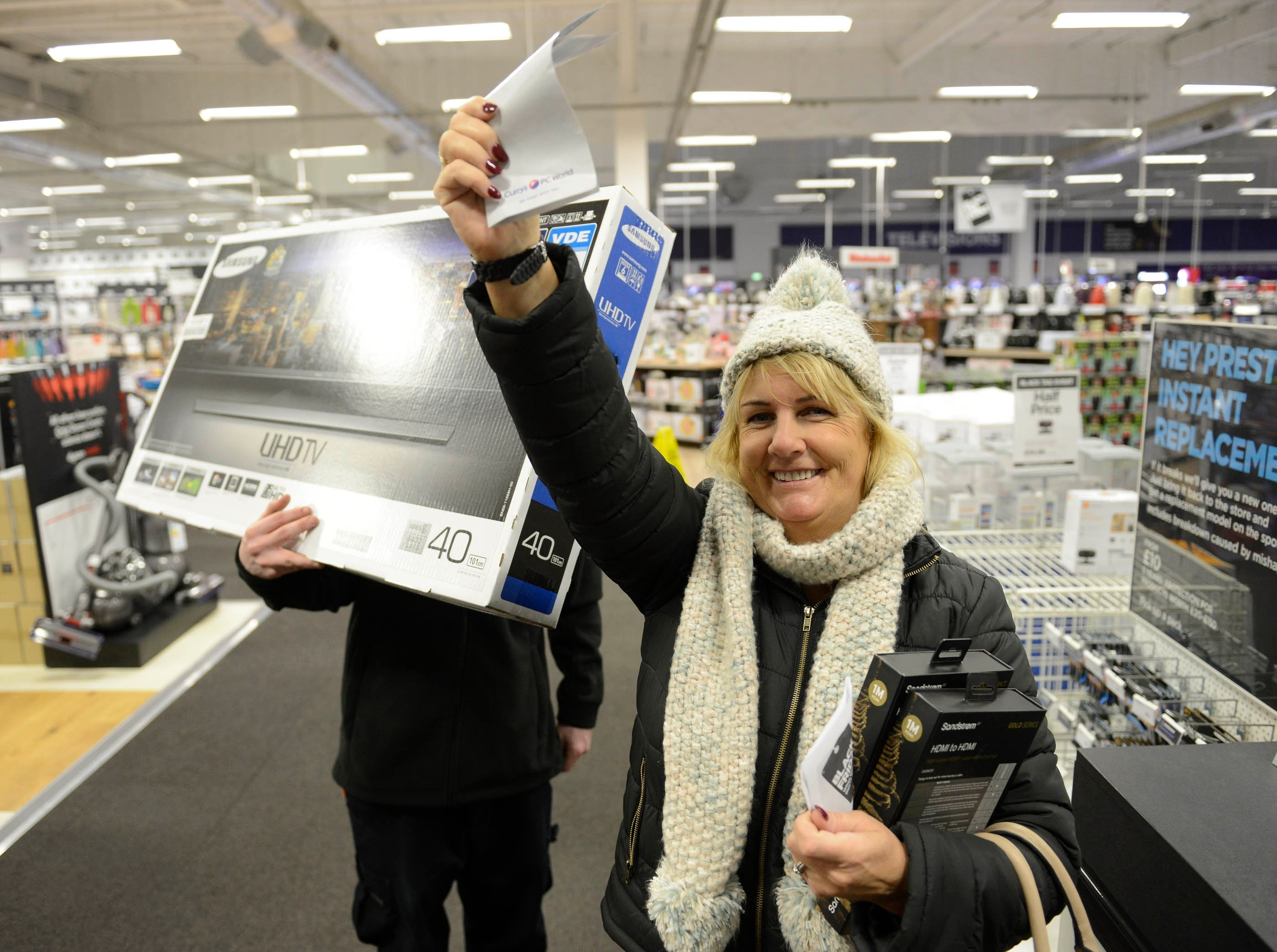 Jacqueline Wilson, 54, from Erskine, one of the first customers in the shop, bags a bargain at Currys PC World, intu Braehead, Glasgow, for Black Friday sales, November 27, 2015. Large crowds did not materialise despite the bargains on offer with very few shoppers being in the store shortly after opening at 6am.