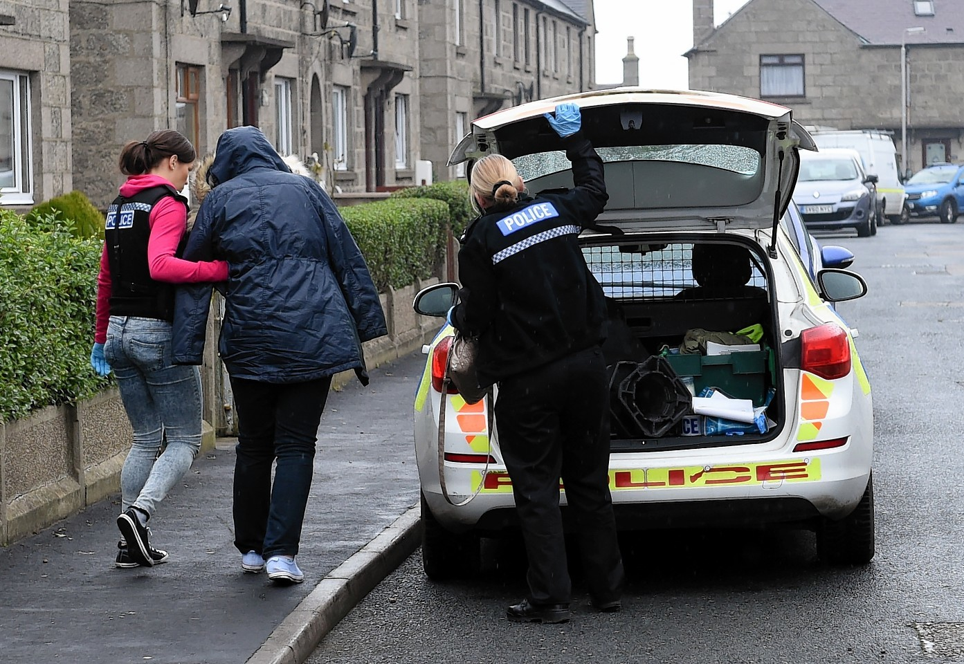 Police lead a suspect away following one of the raids
