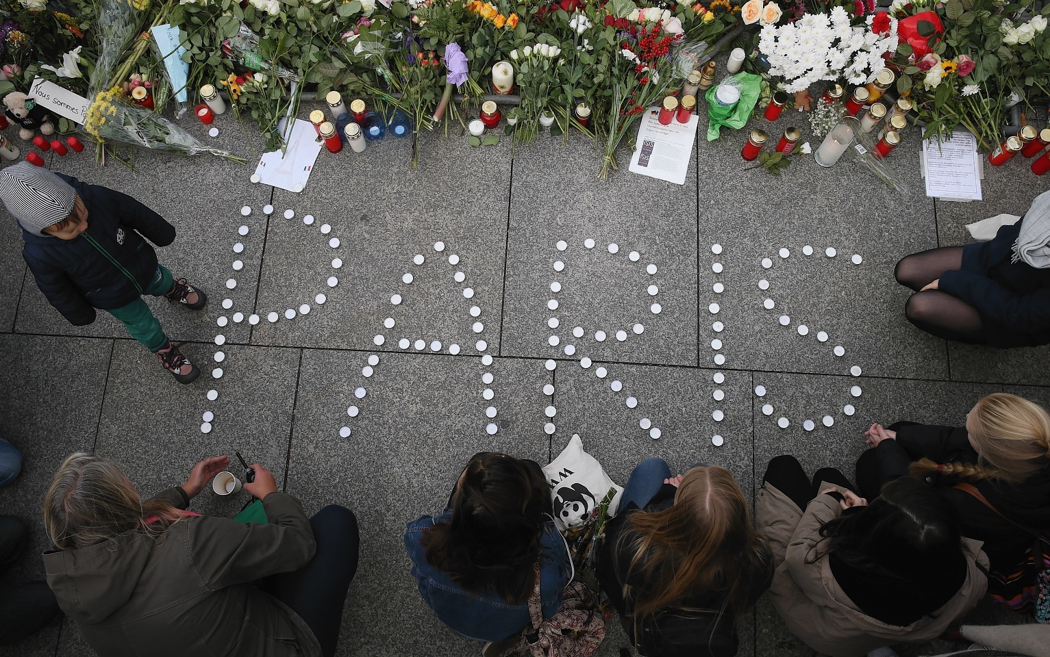 """People finish arranging candles into the word """"Paris"""" next to flowers and messages left at the gate of the French Embassy"""