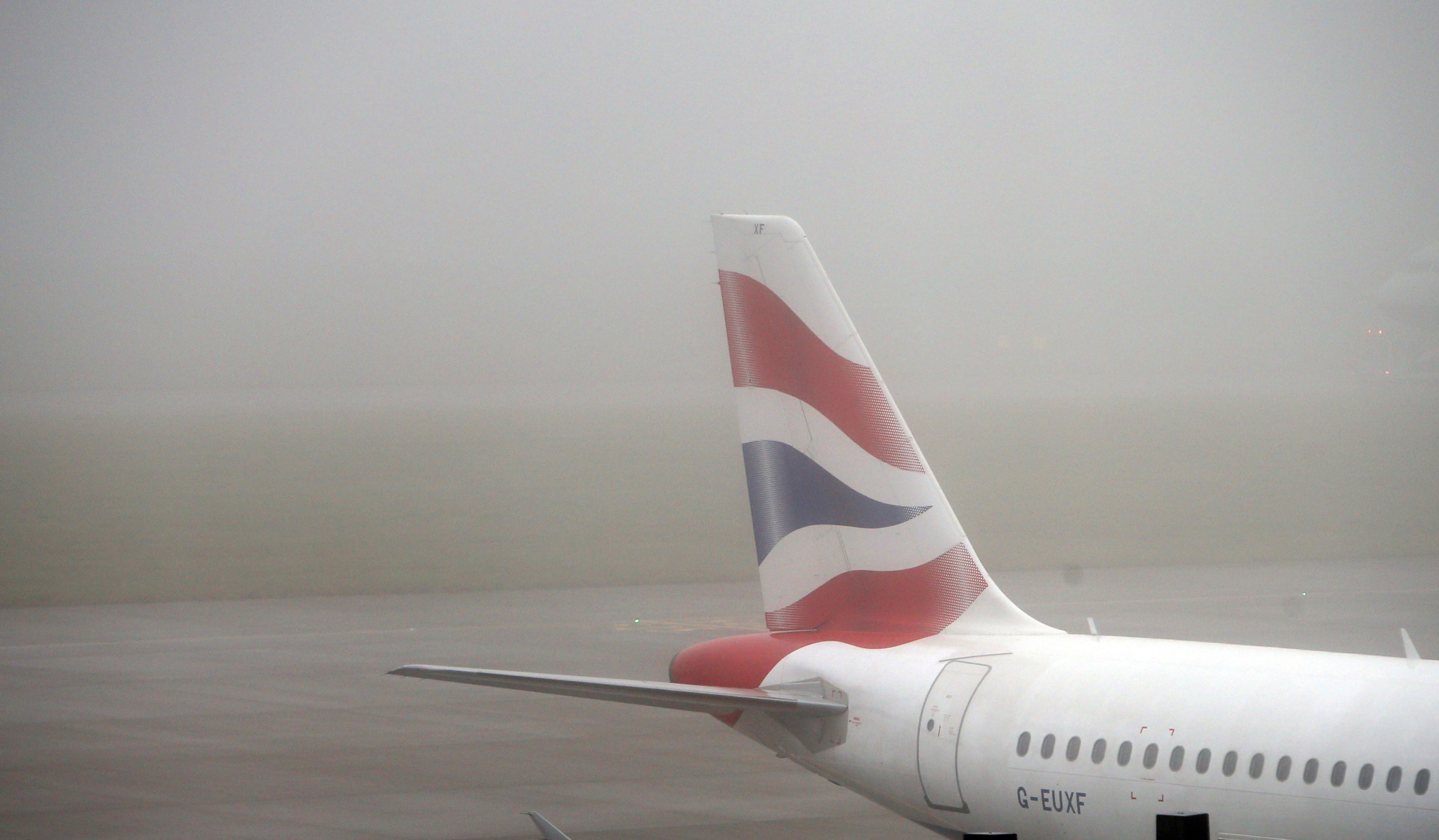 A British Airways plane in the fog at  Terminal 5 of Heathrow Airport, as thick fog disrupts flights at UK airports for a second day.