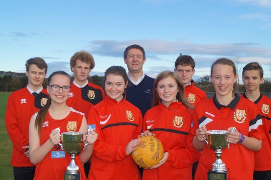Jonathon Milne, director of the FM group, with Mackie Academy pupils after the firm sponsored the school's new sports kit