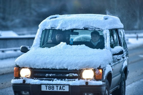 A car covered in snow seen driving in wintery conditions near Craigellachie, Moray in 2015.