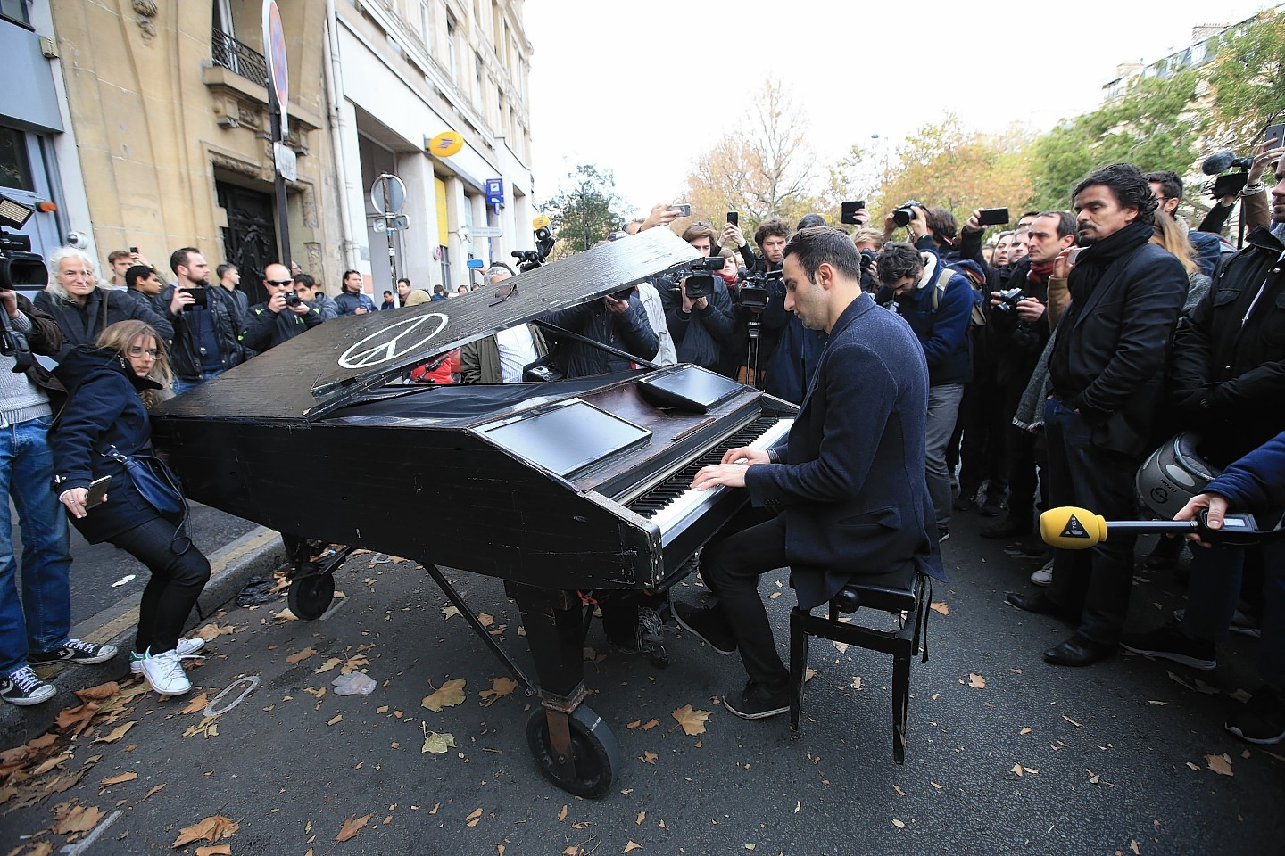 An unnamed man brings his portable grand piano and plays John Lennon's Imagine by the Bataclan, Paris, one of the venues for the attacks