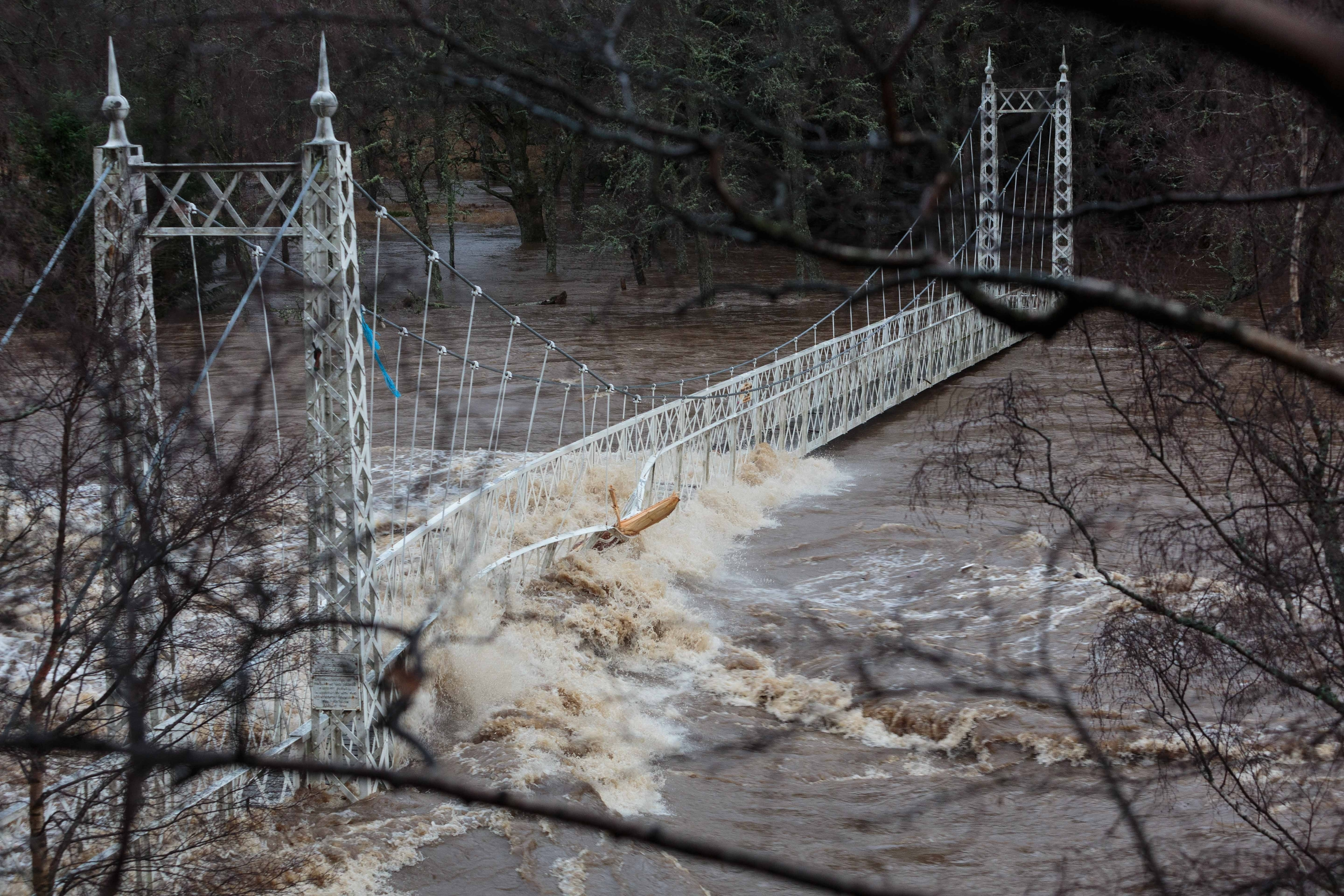 Thousands of homes in Scotland have been left without power as Storm Frank sweeps the country bringing heavy rain and gale-force winds. Pictured: The Cambus O'May footbridge over the River Dee
