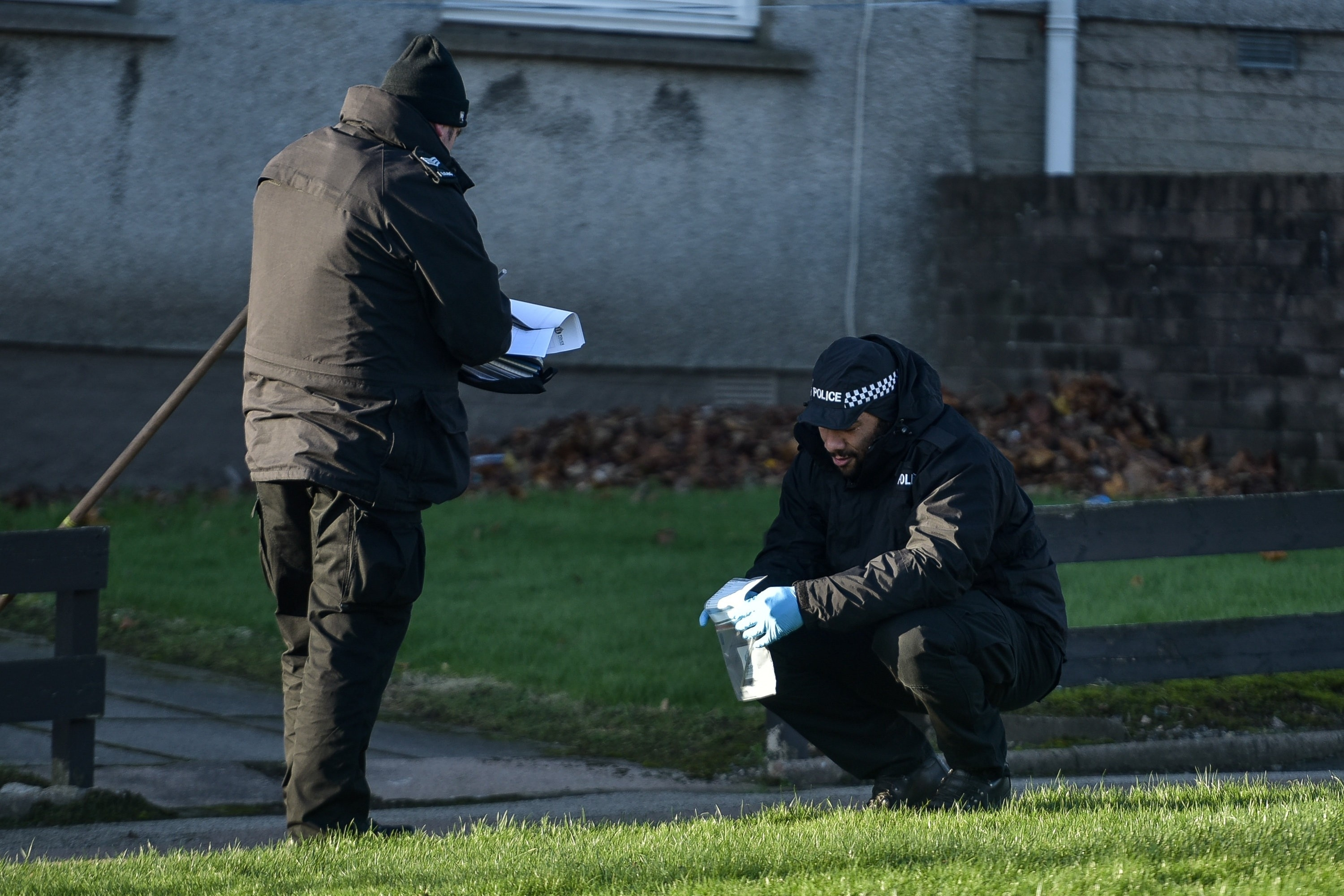 A Police officer is seen with a metal object in an evidence bag on Foresterhill Road