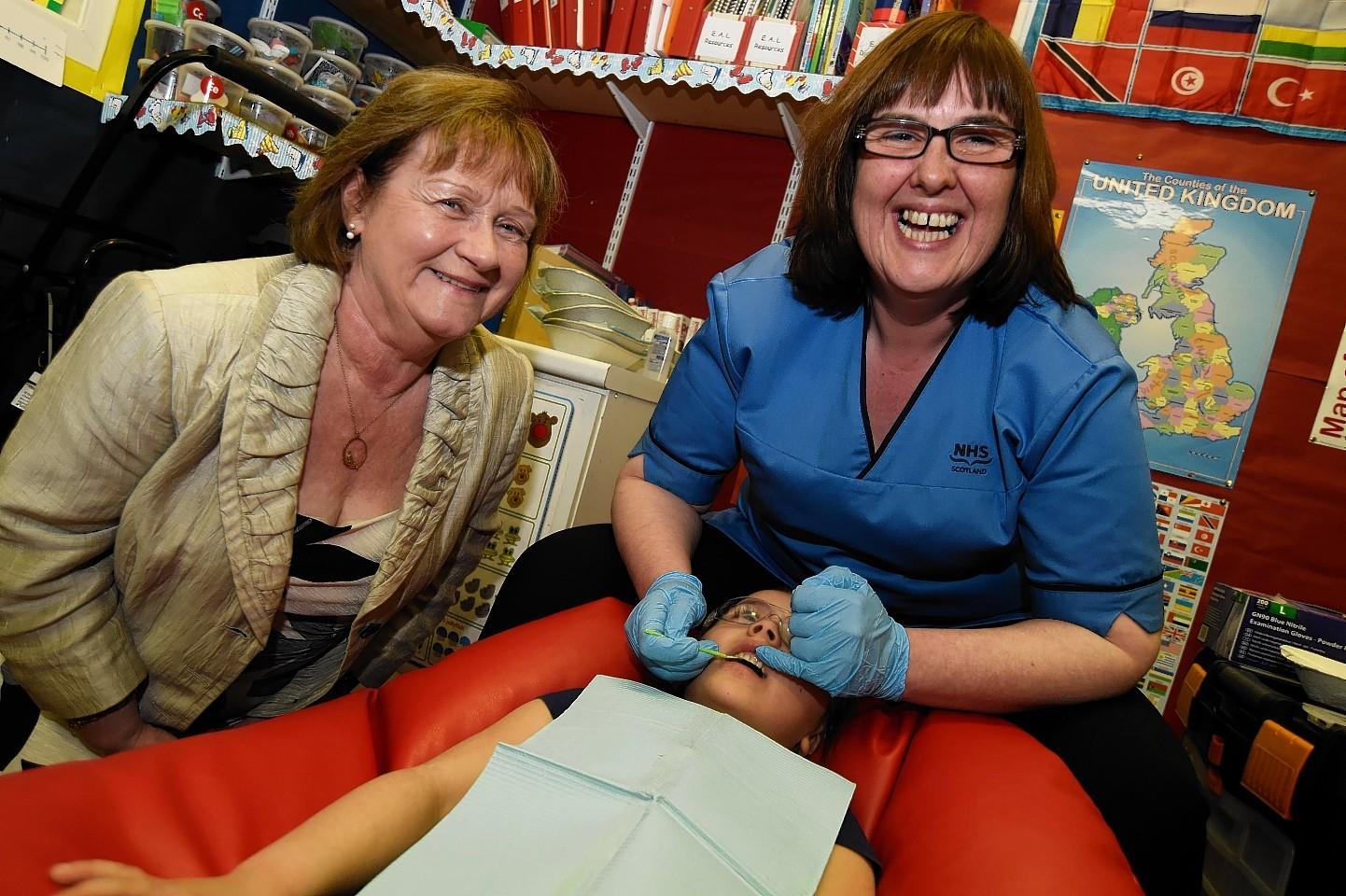 Public health minister Maureen Watt, dental nurse Paula Buchan and Peterhead Central School  Nursery pupil Sophia McAllister