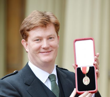 Sir Daniel Alexander holds his insignia of Knighthood which was presented by the Prince of Wales at the Investiture ceremony in Buckingham Palace,