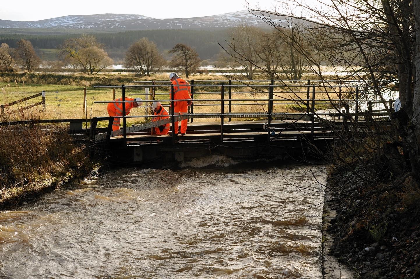 Engineers examine the rail track near Kingussie after flood concerns