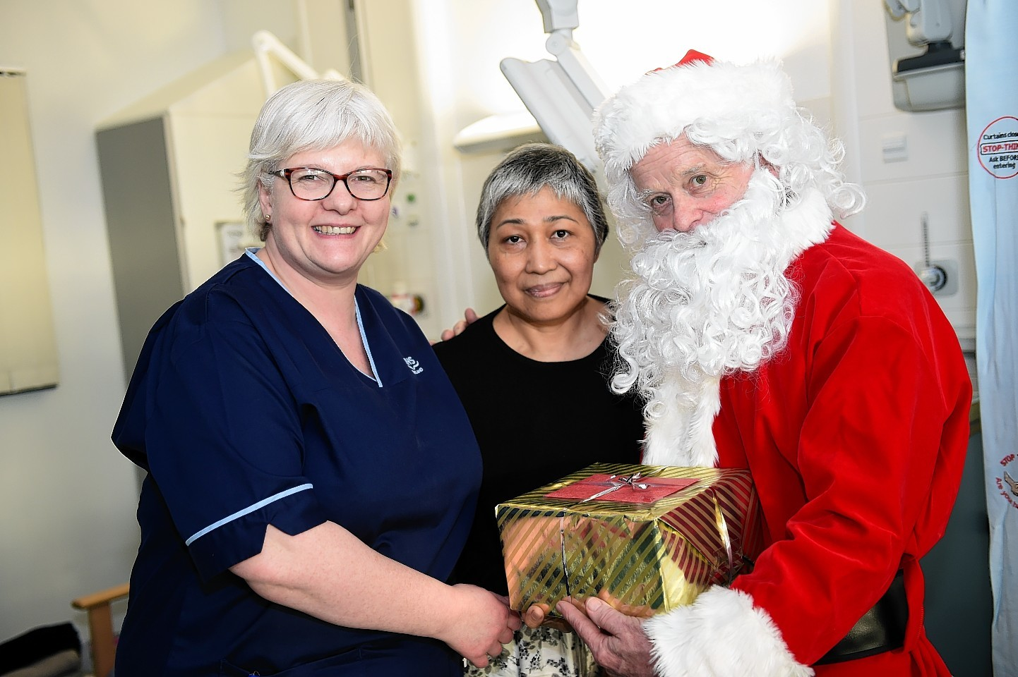 enior Charge Nurse Caty Smith with Patient Tenny Rolinson who gets a christmas present from Santa in Ward 114. Picture by Kami Thomson