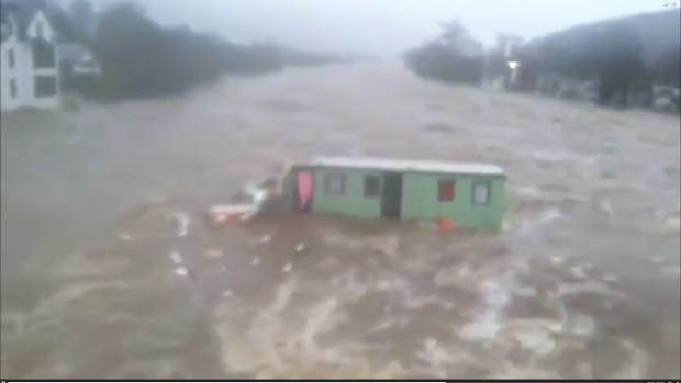 Caravan floating down River Dee, in Ballater, during Storm Frank