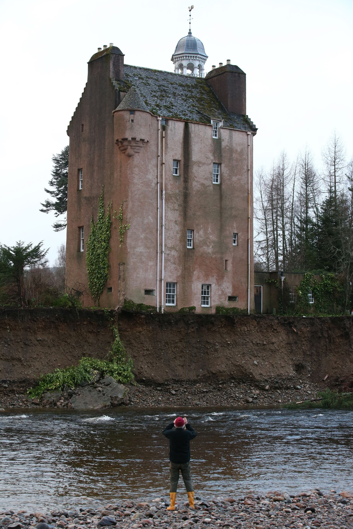 A man takes a picture of Abergeldie Castle on the River Dee after storms last week came close to washing it away. PRESS ASSOCIATION Photo. Picture date: Wednesday January 6, 2016. Photo credit should read: Andrew Milligan/PA Wire