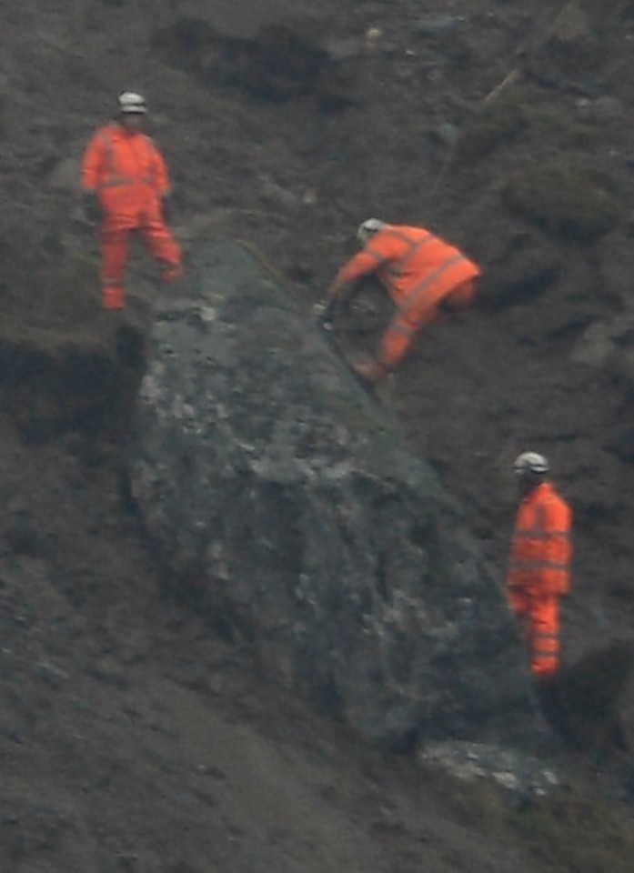 Workmen prepare to detonate the huge boulder above the Rest and be Thankful